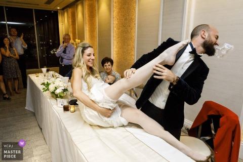 Sydney, Australia groom gets the garter at the wedding reception
