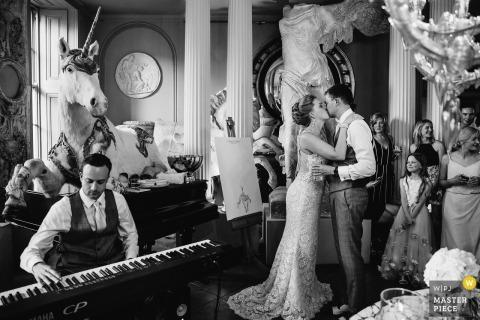 Aynhoe Park bruid en bruidegom kussen terwijl de muzikant piano naast zich speelt