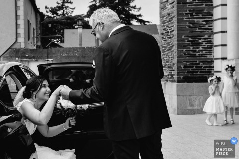Angers brides father helping her get out of the car while in her dress