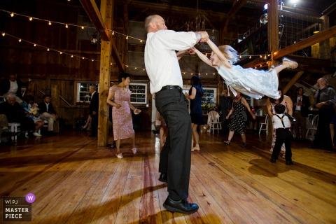 Bruidegom schommelt rond klein meisje op de dansvloer in The Barn at Harvest Moon Pond, Poynette,