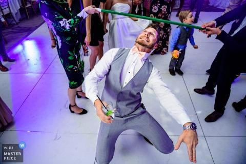 Le marié de Los Angeles joue les limbes tout en tenant un verre à la réception de mariage