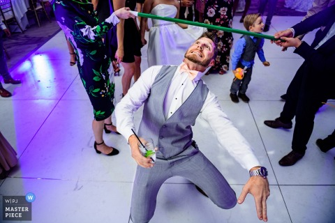 Los Angeles groom plays limbo while holding a drink at the wedding reception