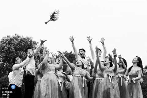 Fujian guests fight for the bouquet at the wedding reception outside