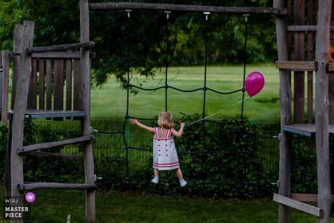București girl holds a ballon while playing on a play set at the wedding