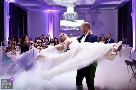 bucuresti groom carries the bride while they dance at the wedding reception