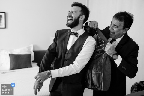 Portugal Ovar groom laughing and getting help with tux before the wedding
