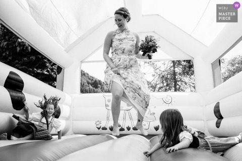 Steinen, Germany bride playing with kids in a bounce castle while in her dress