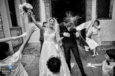 Padova, Italy guests throw rice at the bride and groom after the wedding ceremony outside