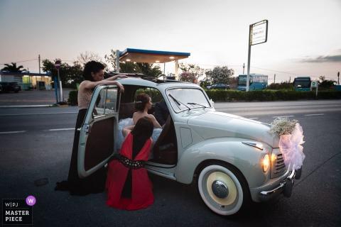 Amantea bridesmaids helping the bride get into the car outside