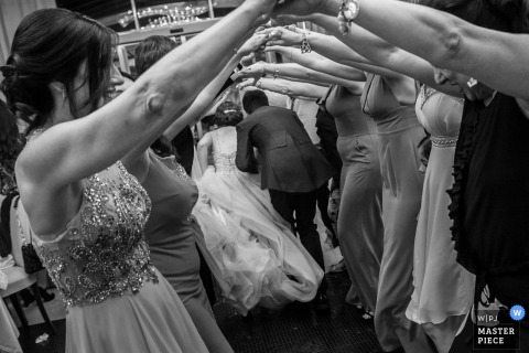 La novia y el novio de Amantea caminan debajo de los invitados que conectan los brazos.