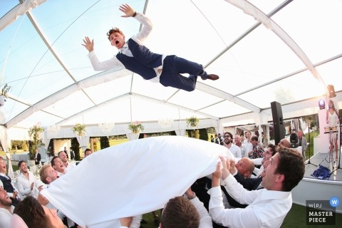 Bari guests throw the groom into the air at the wedding reception