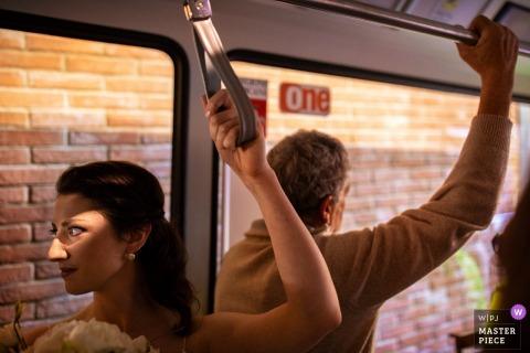 Certaldo, Tuscany bride holds onto the safety strap on a bus