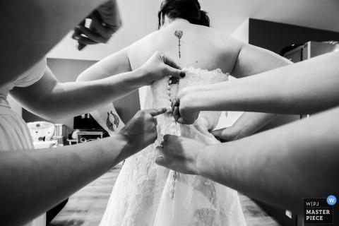 Aubenas, France demoiselles d'honneur aidant la mariée avec sa robe avant la cérémonie de mariage