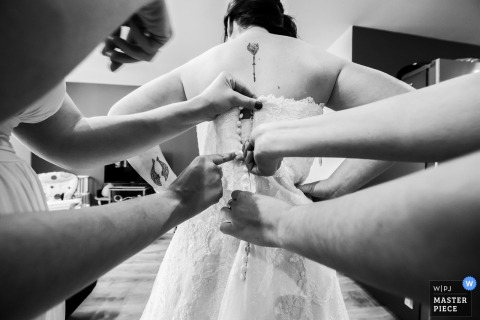 Aubenas, France bridesmaids helping the bride with her dress before the wedding ceremony