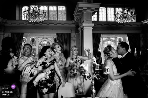 Nottinghamshire, UK bride and groom kiss as the bridal party cheers