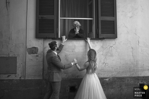 Italy, Naples bride and groom talk and hold hands outside