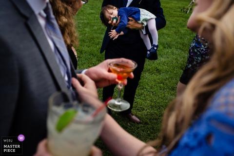De foto van huwelijksgasten die van cocktailuur genieten als slaapkind wordt gehouden bij dit Grote Eiland, het huwelijk van Vermont.