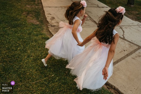 Photo of flower girls holding hands and walking across the grass at a Ciudad de Victoria, Mexico wedding reception.
