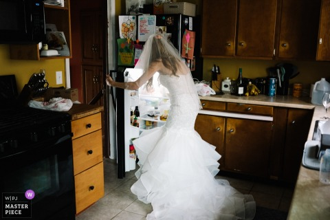 Photo of the bride hitting the refrigerator in her dress before her New York wedding.