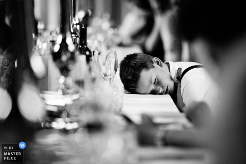 Photo of a boy sleeping on a table at the wedding reception at the Sudeley Castle, United Kingdom