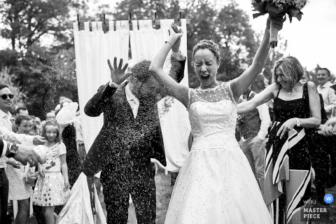 Photo of guests throwing rice at the bride and groom after the wedding ceremony in Chateau de Miremont, Auvergne, France