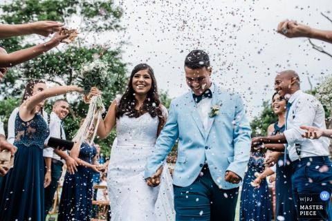 Bride and groom hold hands as guests throw confetti on them after the wedding in Rio de Janeiro