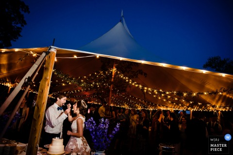 Outdoor photo of bride and groom sharing the wedding cake at the tent reception in Greensboro, Vermont