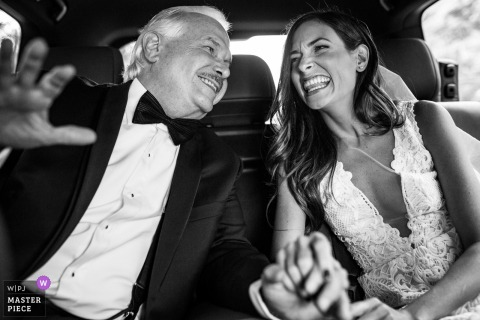 Bride and her father laugh and hold hands while in the car at the wedding in Granada, Nicaragua