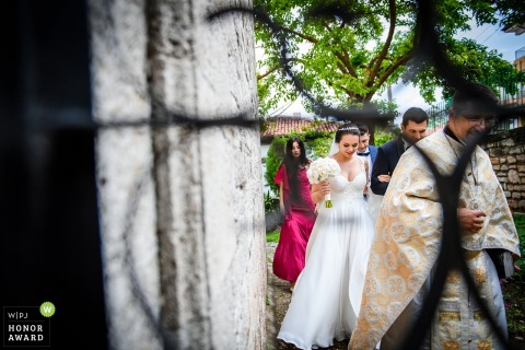 Varna, Bulgaria wedding photographer - the bride and groom follow the priest through the courtyard to the ceremony