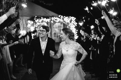 Die Braut und der Bräutigam verlassen ihren Hochzeitsempfang unter einem Handschuh Wunderkerzen in Minneapolis, MN
