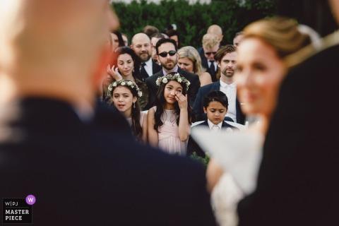 Openluchtfoto van gasten die emotioneel worden tijdens de huwelijksceremonie in New Rochelle, NY