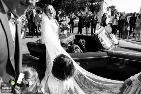 Rambouillet, France wedding photo of a bride laughing as she prepares to enter a small convertible car with her long veiled train