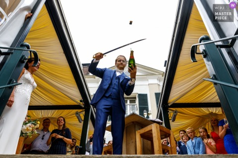ommen groom uses a sword to open bottle of champagne at the wedding reception