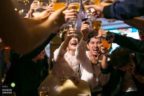 Malaysia bride and groom are surrounded by toasting friends and family in this wedding reception photo
