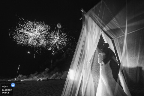Viareggio bride and groom hug as they watch fireworks outside at their night reception.