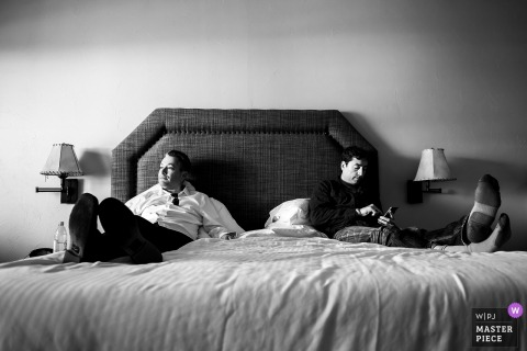 Picture of groom and best man laying on bed before the wedding ceremony at the Table Mountain Inn