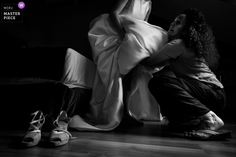 Foto de una mujer ayudando a la novia a ponerse el vestido antes de la boda en Sigüenza, Castilla-La Mancha.