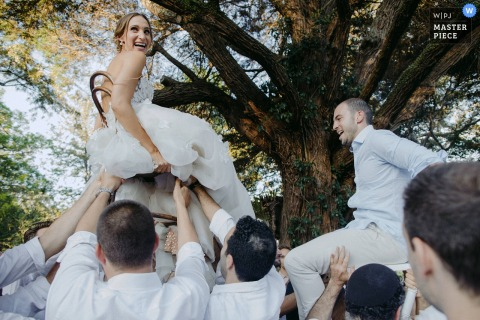 Guests lift the bride and groom in their chairs outside at the wedding reception in Berry, Australia