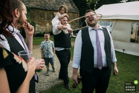 Stanway House, Cheltenham outdoor wedding reception - photographer captured guests playing with children and hula hoops