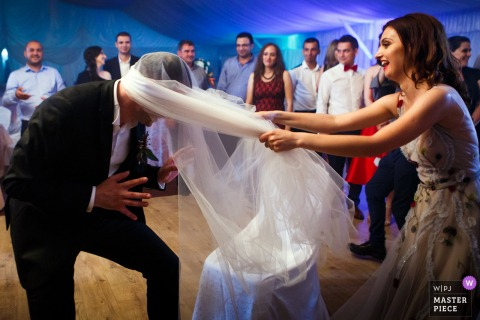 Photo of bride and groom playing games at the wedding reception in Slatina, Romania