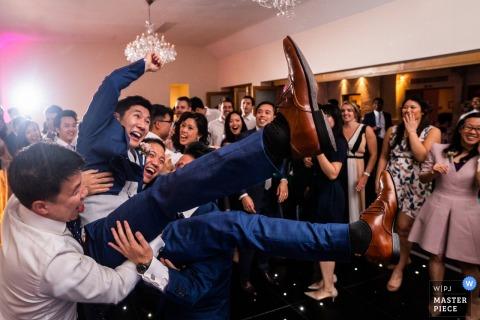 Foto van gasten die de bruidegom rond dragen bij de huwelijksreceptie bij het Botleys Mansion, Engeland