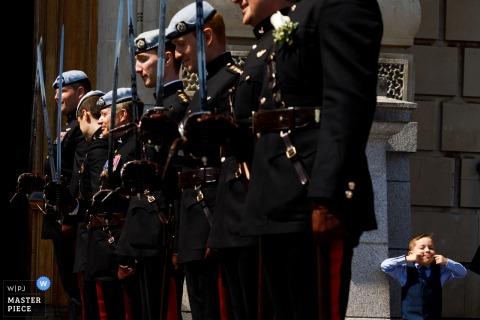 De jongen die van Devon gezichten achter militairen maakt bij de bruiloft