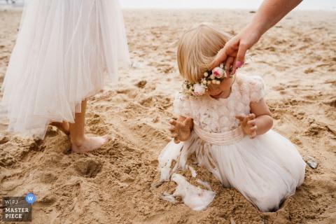 Cornwall-huwelijksceremonie op het strand met bloemmeisjes die in het zand spelen