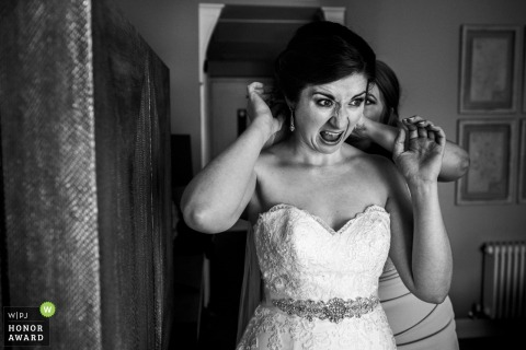 Devon wedding photographer captured this bride in anguish as her veil comb is attached