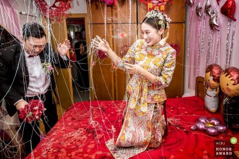 Fotografia ślubna Zhengzhou Henan - gdy nadchodzi pan młody, drużbowie rozpylają pieprz w powietrzu i zmieniają pomieszczenie na pająk w drugim. Z drażniącym zapachem panna młoda uśmiecha się, a pan młody prawie płacze.