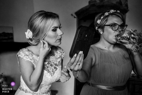 Bridesmaid holds a mirror for the bride getting ready before the wedding in Tenuta di Papena, San Galgano, Siena