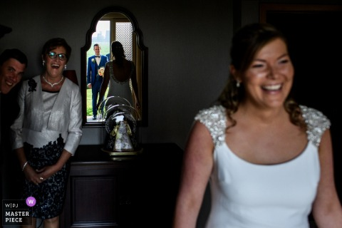 Flanders wedding photographer captured this reflected image of the bride showing her dress for the first time