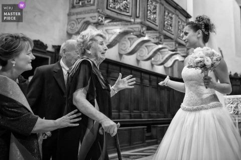 Fotograf ślubny Marche uchwycił ten obraz panny młodej witając gości w kościele