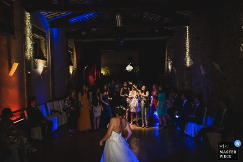 The brides bouquet finds its way toward the single ladies in this Cagliari, Sardinia wedding reception party photograph