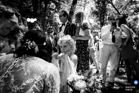 The flower girl talks with the bride and groom at this Chateau Dumas, France outdoor wedding reception